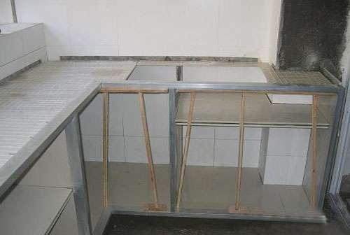 瓷磚櫥柜制作過程 1、計算好立柱位置。 2、瓷磚上開槽,增加隔板用。 3、固定地柜立柱。 4、臺面瓷磚打底,注意灶、水槽的開孔尺寸。 5、安裝隔板。 6、鋁方管加木方,安裝柜門用。 7、固定鋁方管位置。 8、臺面上放鋼筋、水泥找平。 9、裝柜門、吊柜。 10、臺面安裝。 11、柜門擦色。